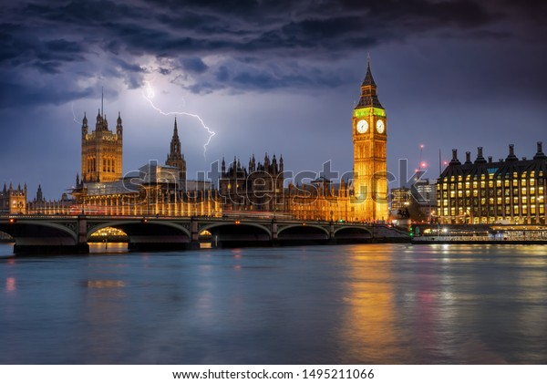 The Westminster Palace and Big Ben clocktower in London by night during a thunderstorm with lighting and dark clouds, UK