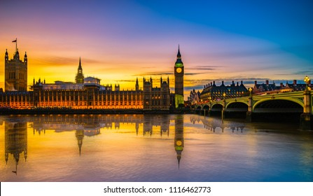 Westminster Palace and Big Ben reflected in the water at beautiful sunset in London