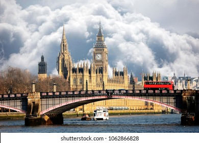 Westminster Palace and Lambeth Bridge over moody dramatic sky with heavy dark stormy clouds building up. An iconic red bus running through the bridge and Big Ben clock tower in the background.