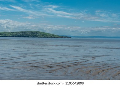 Weston-Super-Mare, UK - June 2, 2018: Brean Down and tidal markings in the soft beach sand.