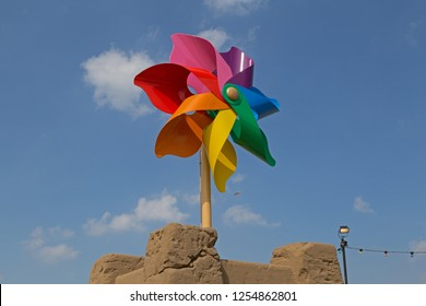 WESTON-SUPER-MARE, UK - SEPTEMBER 10, 2015: A sculpture of a child's pinwheel on top of a sandcastle at Dismaland, an exhibition curated by the artist Banksy at the Tropicana, the town's former lido.