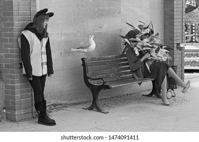 WESTON-SUPER-MARE, UK - SEPTEMBER 10, 2015: An attendant standing next to a sculpture of a woman being attacked by seagulls at Banksy's Dismaland exhibition.