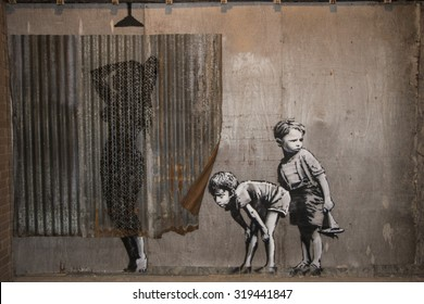 WESTON-SUPER-MARE, UK - SEPTEMBER 21, 2015: Dismaland, Banksy inpired theme park, Weston-Super-Mare, Somerset. A stencil mural by Banksy depicting boys spying on a woman having a shower