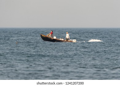 Westport, Massachusetts, USA - July 22, 2017: Recreational fishing boat with two fishermen passing southern end of Gooseberry Neck on foggy summer morning