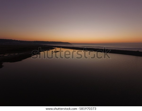Westward Ho Beach, Devon - December 29th 2016 - The sun is setting over the beach after a beautiful sunny day while the water in the pond is still and perfectly reflects the winter sky.
