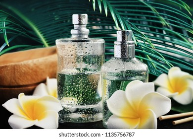 Wet aroma body spray perfume glass bottles with tropical flower decor and dark palm leaf background. Holistic aromatherapy and relaxing spa. Soft focus front bottle