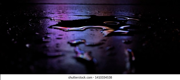 Wet asphalt, night scene of an empty street with a little reflection in the water, the night after the rain. Abstract dark neon background with a wet surface, reflection, neon, glare, blurred bokeh.