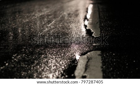 wet asphalt with old road markings at night