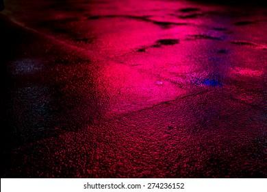 Wet asphalt with puddles close up
