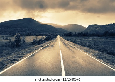 Wet asphalt road in valley against mountains at rainy day. Filtered image.