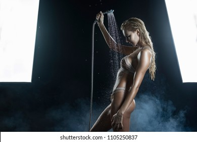 Wet athletic big breasted blonde girl wearing white sexy translucent bikini  washes under the shower spray, which she holds in her hands in scenic smoke on black. Copy space. Advertising design.