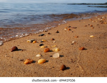 Wet beach pebbles on top of the sand sparkle in the sunlight at the water's edge with gentle, bubbling tides rolling in.