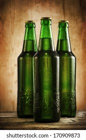 Wet beer bottles on rustic wooden table