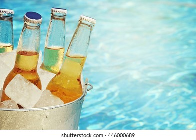 Wet bottle of beer on watter pool in the summer day