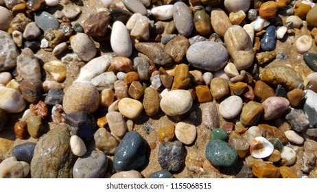 Wet brown gray and blue green pebbles and seashells on wet beach sand. Natural sea stones closeup. Beach smooth pebbles macro. Tourism and travel themed. Beach vacation background.
