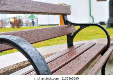 Wet brown wooden bench after the rain in the park