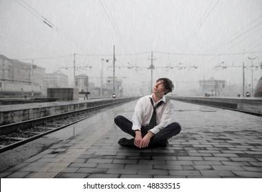 Wet businessman sitting on the platform of a train station