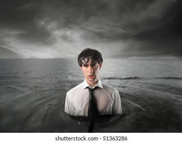 Wet businessman standing in the water