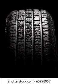 Wet car tyre on black studio background