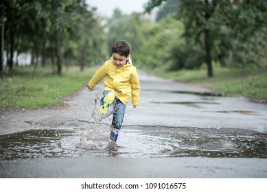 A wet child is jumping in a puddle. Fun on the street. Tempering in summer. Splashes, drops of water, outdoor. waterproof boots jump in puddle and mud in the rain.