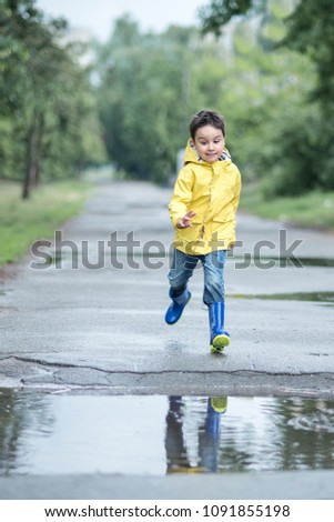 c8e1d97796f051 A wet child is jumping in a puddle. Fun on the street. Tempering in summer.  Splashes, drops of water, outdoor. waterproof boots jump in puddle and mud  in ...