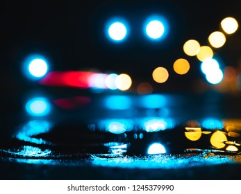 Wet city streets at night, with puddle reflecting the lights and blurry background