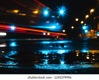 Wet city streets at night, with puddle reflecting the lights, light trails of a car and street lamps