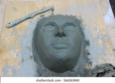 wet clay mask lies on the table of the sculptor