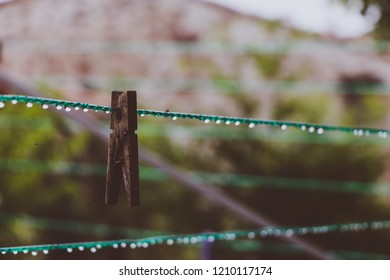 Wet clothes peg clothpin on clothesline in rain