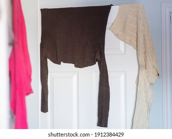 wet clothes are shown drying on a door in an apartment