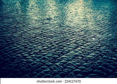 Wet cobblestone street at night