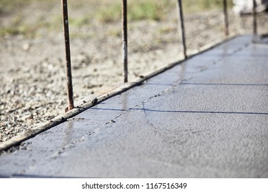 A wet concrete slab with a newly edged side and shallow depth of field