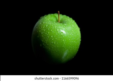 Wet droplets on green granny smith apple with black background
