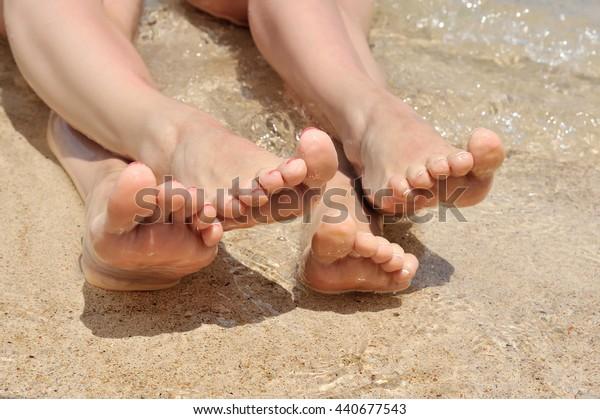A wet female feet on the beach and sand