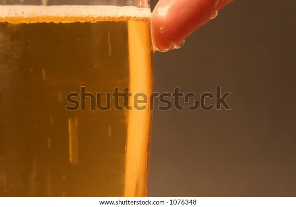 A wet finger on a cold glas of beer