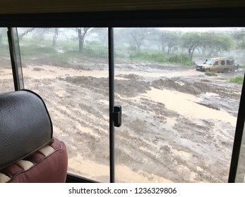 Wet flooded road. Soil erosion after storm, view thru the sliding window of four-wheel drive safari vehicle at Serengeti National Park in Tanzania, East Africa