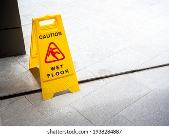 Wet floor caution sign on walkway near the building after raining. Warning yellow plastic caution wet floor sign on the ground with copy space. - Shutterstock ID 1938284887