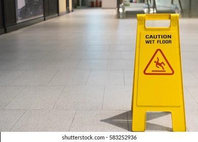Wet floor caution sign on pathway in office