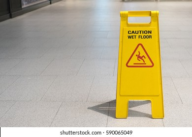 Wet floor caution sign on pathway in office.