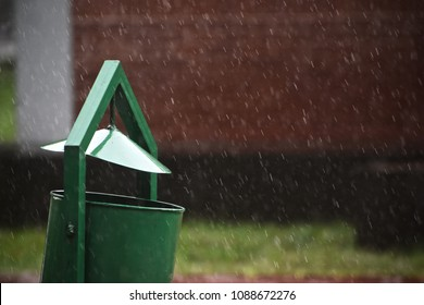 A wet green dustbin isolated metallic object in the rain unique stock photograph