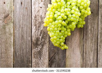 Wet green grapes on old wooden background. Rustic style. Selective focus