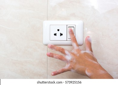 Wet hand of children trun on electric switch. Concept of do not use electricity with wet hand and safety of children.