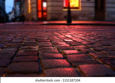 Wet illuminated by red light cobblestone street at night