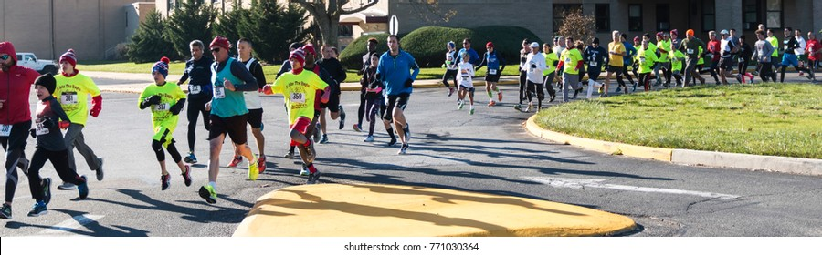 Wet Islip, NY, USA - 24 November 2017: The annual Run Your Turkey Off 4K road race with runners starting in a parking lot and entering the road to run through the neighborhood.