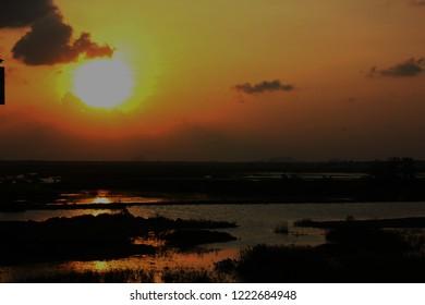 wet land with sun set sky background