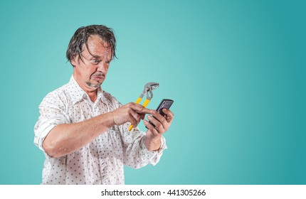 wet man with pipe wrench looking at smartphone for help