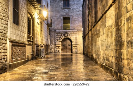 Wet, narrow and dark street in gothic quarter, Barcelona, Spain