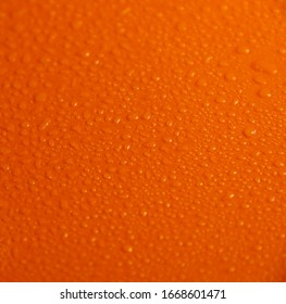 Wet orange background. Bright texture with water drops.