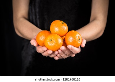 Wet orange tangerines in woman hands with water drops on black background