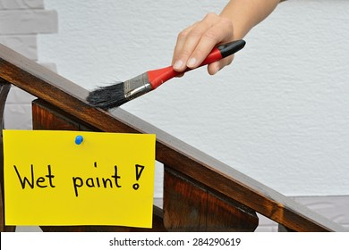 Wet paint sign in front of a painted handrail